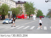 Купить «Tyumen, Russia, on May 9, 2019: Girls cross the road on the crosswalk», фото № 30803204, снято 9 мая 2019 г. (c) Землянникова Вероника / Фотобанк Лори