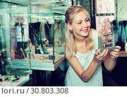 Купить «Portrait of young cheerful woman choosing earrings», фото № 30803308, снято 21 мая 2019 г. (c) Яков Филимонов / Фотобанк Лори