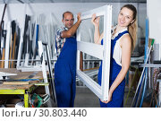 Workers with plastic window frame in assembly shop. Стоковое фото, фотограф Яков Филимонов / Фотобанк Лори