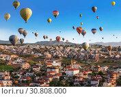 Воздушные шары, пролетающие над небольшим городом Гереме в Каппадокии, Турция (2015 год). Редакционное фото, фотограф Наталья Волкова / Фотобанк Лори