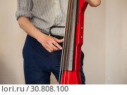 Купить «Man plays red electric contrabass», фото № 30808100, снято 18 мая 2019 г. (c) EugeneSergeev / Фотобанк Лори