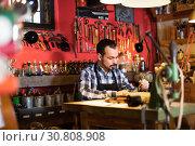 Купить «Male worker working on leather for belt in leather», фото № 30808908, снято 21 августа 2019 г. (c) Яков Филимонов / Фотобанк Лори