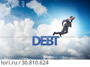 Купить «Debt and loan concept with businessman walking on tight rope», фото № 30810624, снято 17 ноября 2019 г. (c) Elnur / Фотобанк Лори