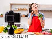 Купить «Young female vegetarian recording video for her blog», фото № 30812196, снято 22 февраля 2019 г. (c) Elnur / Фотобанк Лори