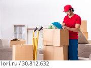 Купить «Young male contractor with boxes working indoors», фото № 30812632, снято 12 ноября 2018 г. (c) Elnur / Фотобанк Лори