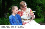 Купить «Grandmother is considering a gift of a granddaughter made of wild flowers», видеоролик № 30815360, снято 6 ноября 2017 г. (c) Aleksandr Sulimov / Фотобанк Лори
