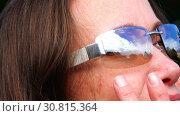 Купить «Lenses of glasses in white frame close the eyes of a woman from the sun», видеоролик № 30815364, снято 5 ноября 2017 г. (c) Aleksandr Sulimov / Фотобанк Лори