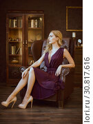 Купить «Sexy young woman in a purple dress sits in a large vintage leather executive chair in an expensive luxury dark interior», фото № 30817616, снято 4 ноября 2017 г. (c) katalinks / Фотобанк Лори