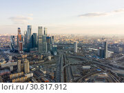 Купить «High-rise buildings and transport metropolis, traffic and blurry lights of cars on multi-lane highways and road junction at sunset in Moscow», фото № 30817912, снято 8 декабря 2019 г. (c) Mikhail Starodubov / Фотобанк Лори