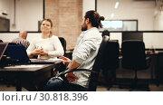 Купить «Focused bearded freelancer concentrated on work with laptop in coworking space with international team», видеоролик № 30818396, снято 12 апреля 2019 г. (c) Яков Филимонов / Фотобанк Лори