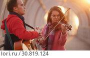 Купить «Woman with violin and man with guitar play and sing on the overhead passage», видеоролик № 30819124, снято 3 апреля 2020 г. (c) Константин Шишкин / Фотобанк Лори