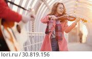 Купить «Woman with violin and blured man with guitar playing classic music on the passage», видеоролик № 30819156, снято 3 апреля 2020 г. (c) Константин Шишкин / Фотобанк Лори