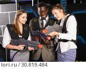 Купить «Smiling associates – afro man and two European women posing at laser tag room», фото № 30819484, снято 4 апреля 2019 г. (c) Яков Филимонов / Фотобанк Лори