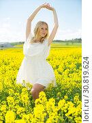 Купить «Happy girl stretch oneself in rape seed flowers field posing in white dress», фото № 30819624, снято 8 апреля 2019 г. (c) Яков Филимонов / Фотобанк Лори