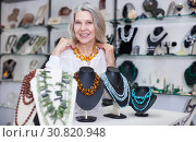 Купить «Woman trying on a aventurine necklace and earrings at a jewelry store», фото № 30820948, снято 2 мая 2019 г. (c) Яков Филимонов / Фотобанк Лори