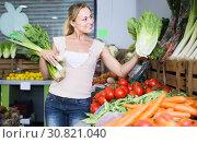 happy young female customer holding fresh celery and leek. Стоковое фото, фотограф Яков Филимонов / Фотобанк Лори