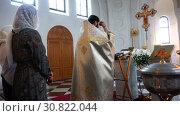 Купить «Father in a cassock recites a prayer at the baptism of a baby», видеоролик № 30822044, снято 12 ноября 2017 г. (c) Aleksandr Sulimov / Фотобанк Лори