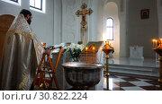 Купить «The holy father reads a prayer in the church before the ritual of baptism», видеоролик № 30822224, снято 12 ноября 2017 г. (c) Aleksandr Sulimov / Фотобанк Лори
