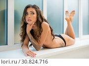 Купить «Slim tattooed girl lying on the window shot», фото № 30824716, снято 6 августа 2017 г. (c) Гурьянов Андрей / Фотобанк Лори