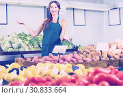 Купить «Woman seller wearing apron showing potatoes», фото № 30833664, снято 18 июля 2019 г. (c) Яков Филимонов / Фотобанк Лори