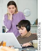 Upset mother arguing with son who plaing video games. Стоковое фото, фотограф Яков Филимонов / Фотобанк Лори