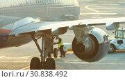Купить «A huge plane standing on the runway on a background of a sunset. A man worker informs that plane is ready», видеоролик № 30838492, снято 9 июля 2020 г. (c) Константин Шишкин / Фотобанк Лори