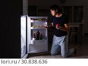 Купить «Man breaking diet at night near fridge», фото № 30838636, снято 8 февраля 2019 г. (c) Elnur / Фотобанк Лори