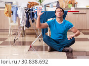Купить «Young man husband doing clothing ironing at home», фото № 30838692, снято 25 февраля 2019 г. (c) Elnur / Фотобанк Лори