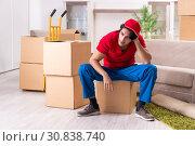 Купить «Young male contractor with boxes working indoors», фото № 30838740, снято 12 ноября 2018 г. (c) Elnur / Фотобанк Лори