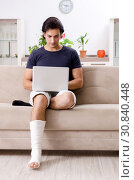 Купить «Leg injured young man suffering at home», фото № 30840448, снято 15 января 2019 г. (c) Elnur / Фотобанк Лори