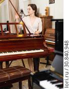 Купить «Saleswoman assistant in piano music store», фото № 30840948, снято 16 апреля 2019 г. (c) Яков Филимонов / Фотобанк Лори