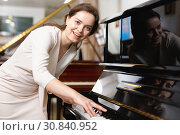 Beautiful girl chooses a piano in a music store. Стоковое фото, фотограф Яков Филимонов / Фотобанк Лори