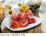 Купить «Rolled up dry-cured ham slices with olives», фото № 30841196, снято 17 июня 2019 г. (c) Яков Филимонов / Фотобанк Лори