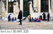 Купить «Grand Place Square schoolchildren of different nations are sitting on the steps near the building», видеоролик № 30841320, снято 24 ноября 2017 г. (c) Aleksandr Sulimov / Фотобанк Лори