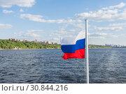 Купить «Flag of Russia against the background of the city and the river», фото № 30844216, снято 21 мая 2019 г. (c) Дмитрий Тищенко / Фотобанк Лори