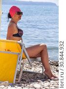 Купить «Привлекательная взрослая женщин сидит на желтом лежаке, солнцезащитные очки на глазах, береговая линия», фото № 30844932, снято 23 июля 2018 г. (c) Кекяляйнен Андрей / Фотобанк Лори