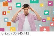 Купить «man touching his head over app icons on grey», фото № 30845412, снято 3 февраля 2019 г. (c) Syda Productions / Фотобанк Лори