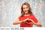 Купить «smiling teenage girl in red making hand heart», фото № 30845448, снято 17 февраля 2019 г. (c) Syda Productions / Фотобанк Лори