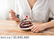 Купить «woman eating piece of layer cake with cherry», фото № 30845480, снято 21 мая 2015 г. (c) Syda Productions / Фотобанк Лори