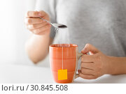 close up of woman adding sugar to cup of tea. Стоковое фото, фотограф Syda Productions / Фотобанк Лори