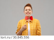 smiling red haired teenage girl with big bowtie. Стоковое фото, фотограф Syda Productions / Фотобанк Лори