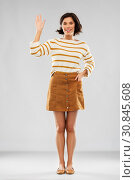woman in pullover, skirt and shoes waving hand. Стоковое фото, фотограф Syda Productions / Фотобанк Лори