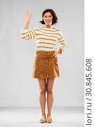 Купить «woman in pullover, skirt and shoes waving hand», фото № 30845608, снято 6 марта 2019 г. (c) Syda Productions / Фотобанк Лори