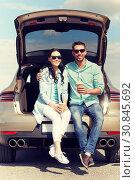 Купить «happy couple with coffee at hatchback car trunk», фото № 30845692, снято 12 июня 2016 г. (c) Syda Productions / Фотобанк Лори