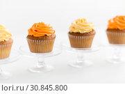 Купить «cupcakes with frosting on confectionery stands», фото № 30845800, снято 6 июля 2018 г. (c) Syda Productions / Фотобанк Лори