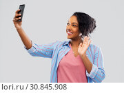 african american woman taking selfie by smartphone. Стоковое фото, фотограф Syda Productions / Фотобанк Лори