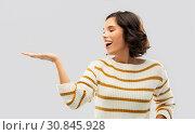 Купить «smiling young woman holding empty palm», фото № 30845928, снято 6 марта 2019 г. (c) Syda Productions / Фотобанк Лори
