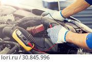 Купить «auto mechanic man with multimeter testing battery», фото № 30845996, снято 1 июля 2016 г. (c) Syda Productions / Фотобанк Лори