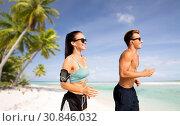 Купить «couple with phones and arm bands running on beach», фото № 30846032, снято 1 августа 2018 г. (c) Syda Productions / Фотобанк Лори