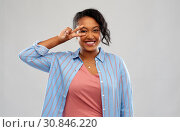 Купить «happy african american woman showing peace», фото № 30846220, снято 2 марта 2019 г. (c) Syda Productions / Фотобанк Лори